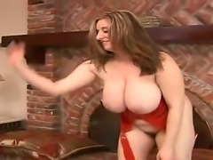 Amazing busty mature whore Kitty Lee showing off her colossal breasts and masturbating her hairy and horny pussy while a handsome man is poring oil on her boobs the size of a planet.
