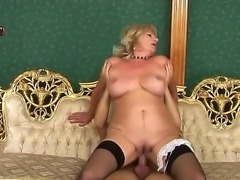 Blonde woman in age is screwing with dude. She stays in stockings and high heeled shoes before feeling big throbbing penis inside of clean shaved old pussy. Watch the scene.