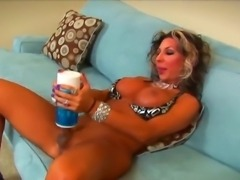 Smoking hot tanned shemale cougar Ariel Everits with big firm hooters and smoking hot body in high heels pleasures herself with kinky jerk off toy in arousing solo action.