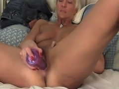 Mature nympho gives her enormous vibrator a workout by shoving it really deep into her wet stretched out shaved pussy.