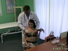 Doctor in his uniform massages stiff neck of hot brunette patient and soon he teases her tits and fucks her pussy on a desk in fake hospital