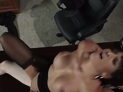A dark haired, big titted Latina milf wearing stockings, Mercedes Carrera, is getting fucked hard by a young stud on his the desk in his office as shes riding his dick.
