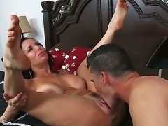 Big breasted beautiful MILF Veronica Avluv spreads her sexy legs invitingly to turn young guy on. He gives her neatly trimmed experienced pussy a lick and then makes his rod disappear in her wet pink hole.