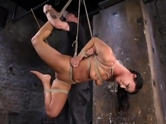 slave hangs from the ceiling and is caned by her sex master