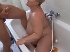 Disgusting fat blondie blows stiff dick of young man in bathroom