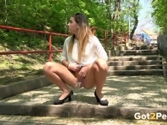 Sexy white summer girl sprinkles on the steps in the park