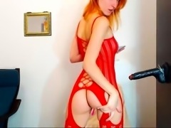 Stunning redhead in lingerie buries a black toy in her ass