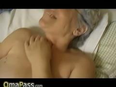 Seductive white haired granny masturbates with dildo in bed
