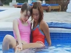 Sweet lesbian girlfriends making love in the pool